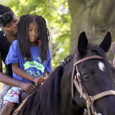 Jasmine Deloney tries to comfort her daughter McKinzie Mundy, 7, as she rides a horse during Smithfest 2019 at Smith Park in Toledo on Saturday, June 22, 2019. THE BLADE/LORI KING