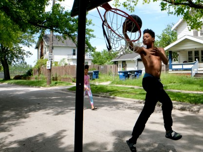 Levelle Stokes, 12, soars to dunk while playing with his sister Shawnkeya Stokes, 11, on the street in front of their Toronto St. home in Toledo on Friday, June 14, 2019. THE BLADE/LORI KING