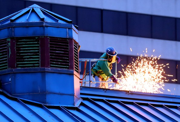 Sparks fly as a worker uses a torch to cut the metal roofing of the enclosed walkway. Workers begin demolition of the Imagination Station's enclosed footbridge over Summit Street in Toledo on Monday, June 17, 2019. THE BLADE/KURT STEISS