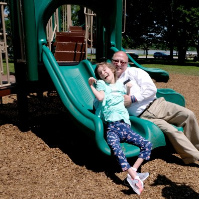 Rossford Mayor Neil MacKinnon slides down the slide with Kaci Schwiefert, 20, on a new inclusive playground at Veterans Park in Rossford, Ohio on Tuesday, June 11, 2019. THE BLADE/LORI KING