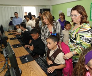 "TRB President Sandra Torres (standing at center) and Caguas Deputy Mayor Lydia E. Denizard-Rivera (right) look on as students ""break in"" the new equipment at the Caguas Internet center."