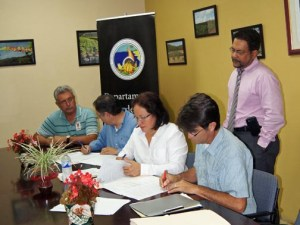 Agriculture Secretary Myrna Comas (center) signs agreements with coffee farmers.