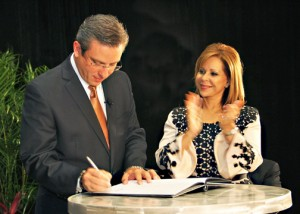 Gov. García-Padilla signs the executive order creating the council, as PRMA President Waleska Rivera looks on.