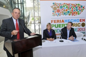 At podium, Puerto Rico Products Association President Manuel Cidre speaks, while María Félix and Secretary of State David Bernier (sitting) listen.