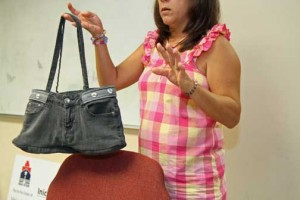 An Apego program participant shows off a hand-made handbag created during her stay at the nonprofit.