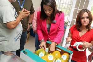 Viviana Mercado, the retailer's corporate affairs manager, inspects a box of papayas.