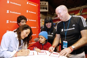 From left: Draco Rosa's wife, Ángela Alvarado and their son Redamo change their names for a cancer patient's as Scotiabank CEO Peter Bessey looks on.