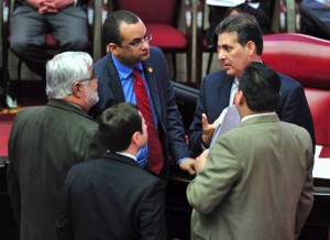 Lawmakers huddle on the Senate floor during a session Thursday to address several measures.