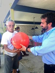 Jaime Pabón, Aerostar's environmental director (right), hands a buoy to fisherman Armengot Rivera.