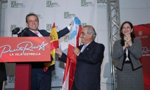 Gov. García-Padilla trades flags with Juan José-Hidalgo, president of Spanish airliner Air Europa, as Puerto Rico Tourism Co. Executive Director Ingrid Rivera looks on.