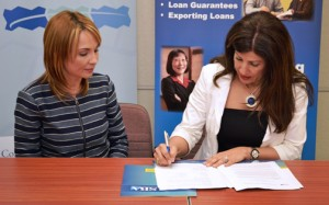María G. Rodríguez, director of housing programs for PathStone, watches as SBA District Director Yvette T. Collazo signs the strategic alliance.