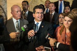 Flanked by NPP lawmakers, Resident Commissioner Pedro Pierluisi reacts following the State of the Commonwealth address.