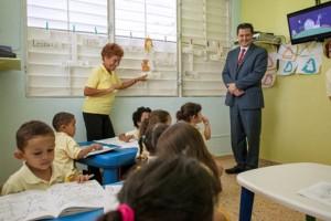 María E.  Guzmán-Millán, pre-kindergarden teacher leads her group of students, as Félix Lugo, country manager of Columbus Business solutions, looks on.