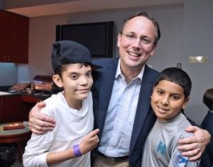 EVERTEC President Mac Schuessler (center), spends time with children who participate in the Ser de Puerto Rico program.