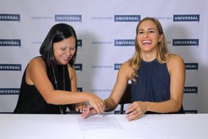 Jocely Vega, COO of Univeral Group and Puig sign the multi-year contract in Dorado.