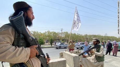 Taliban fighters stand guard at an entrance gate outside the Interior Ministry in Kabul on August 17, 2021.