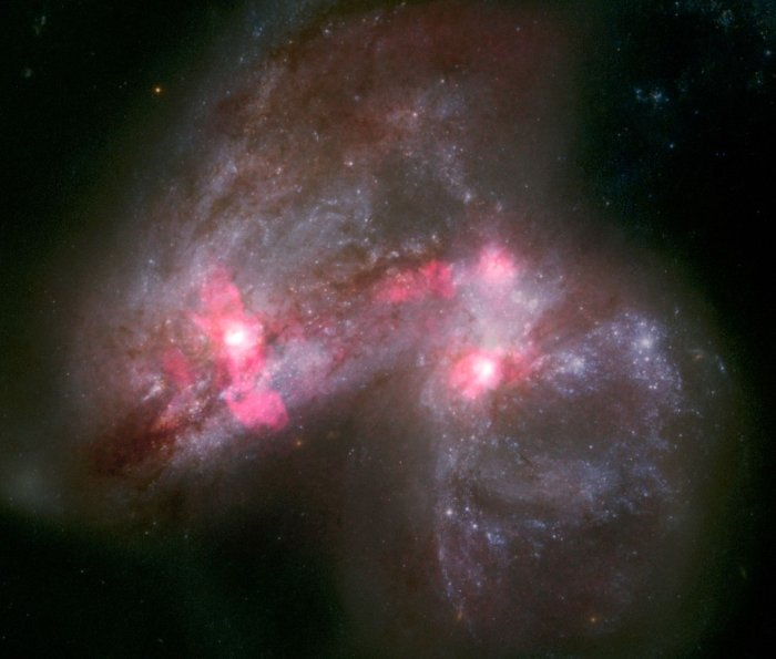 A luminous cloud with pink highlights shows two galaxies merging