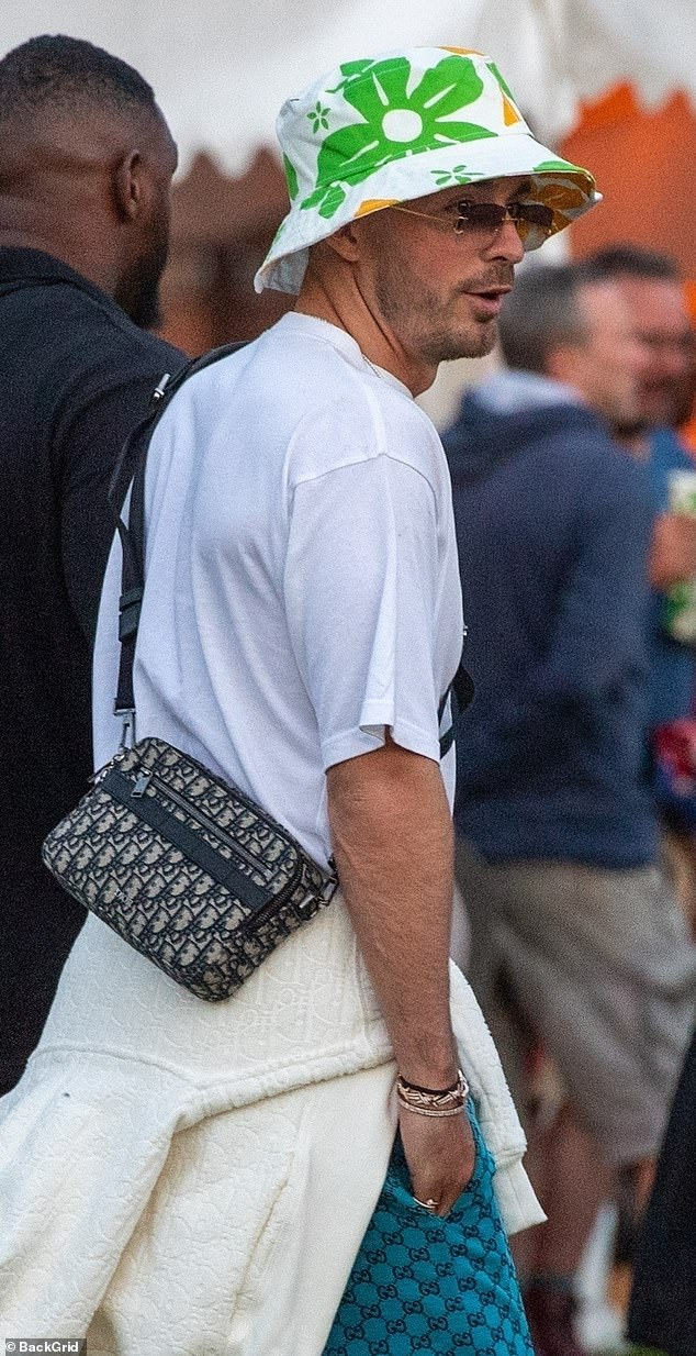 Striking: His look was finished off with a PS1,500 Christian Dior cross-body man bag and a mismatched multi-coloured bucket hat reminiscent of Bill and Ben, the flower pot men
