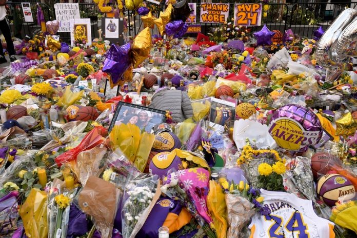 flowers, photos, basketballs, signs, and balloons on the sidewalk for Kobe Bryant