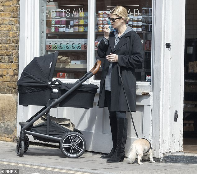 Stepping out: The star waited patiently outside the bakery with her dog after heading out for the walk with her new baby