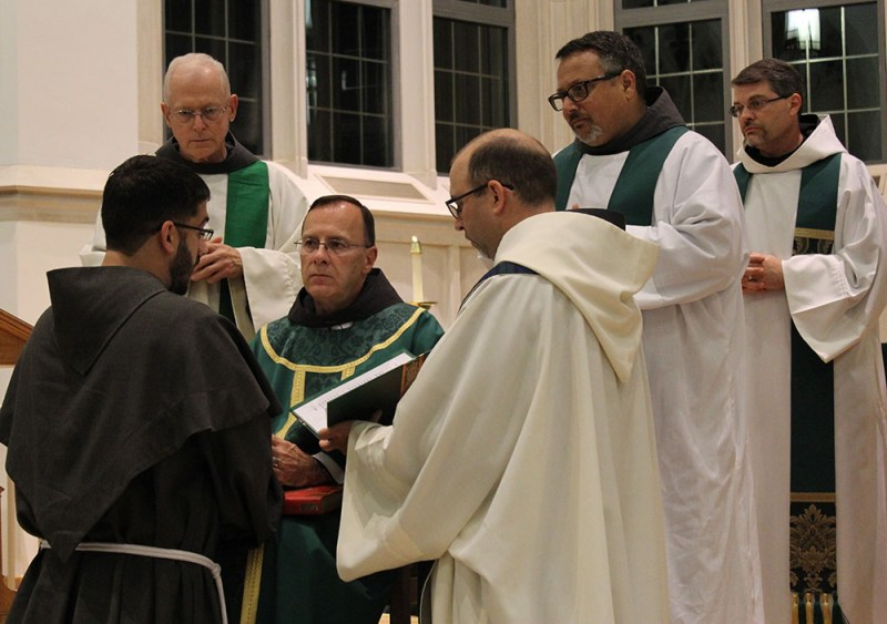 During Mass on July 12th, friar Emanuel Vasconcelos, OFM Conv. (kneeling left) renewed his Simple Vows in front of a congregation of over 100 people, in Duke Divinity School's Goodson Chapel. Fr. Brad Heckathorne, OFM Conv., (seated) St. Anthony Padua Friary Guardian (Duham, NC) received friar Manny's vows as the Minister Provincial's delegate, witnessed by Fr. Andy Santamauro, OFM Conv. (standing right) and Fr. Bill Robinson, OFM Conv. (standing left). Fr. Michael Lasky, OFM Conv. (kneeling right) served as emcee and Fr. Justin Ross, OFM Conv. (standing far right) concelebrated Mass.