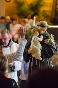 A pilgrim, about to receive the Holy Eucharist, reaches out to touch the statue of St. Anthony, seeking his intercession.