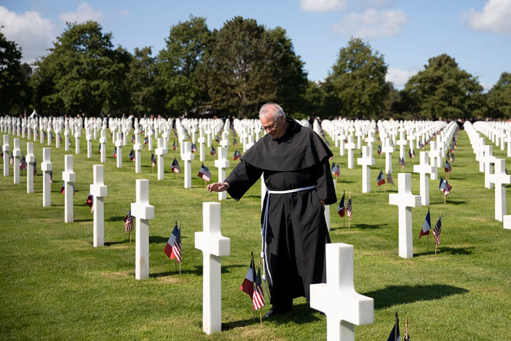 fr. Martin blessing graves at Normandy