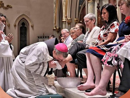 Bishop Gregory Hartmayer, a Franciscan Friar Conventual who serves in the Diocese of Savannah, Georgia, demonstrates the hospitality of Jesus as he washes and kisses the feet of parishioners at Holy Thursday Mass.