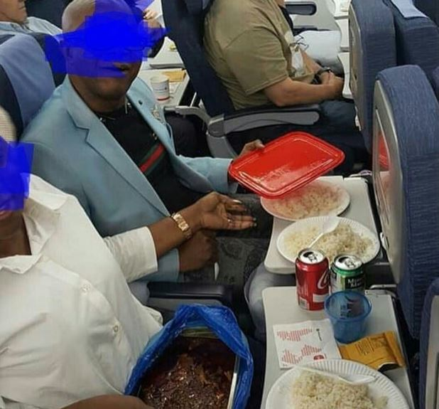 African Couple Seen Properly Serving Themselves With The Food They Brought Aboard A Plane - Photo