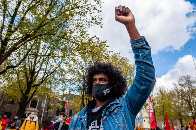 A man is seen raising his fist while wearing a BLM face mask...