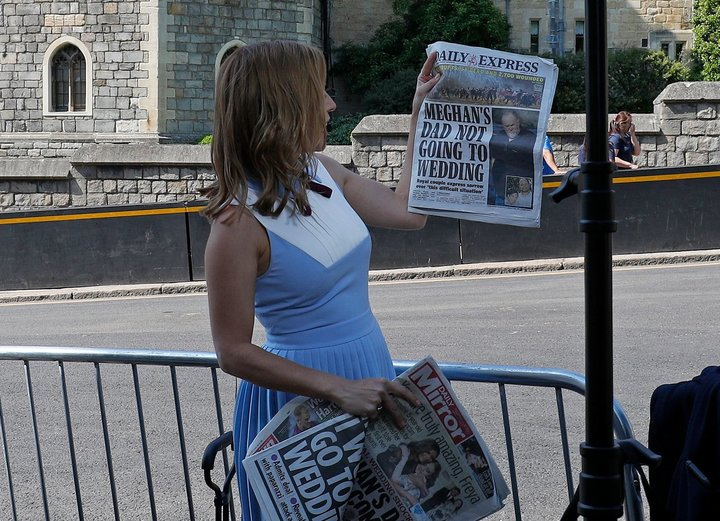 A CNN reporter holds up copies of British newspapers leading with a story on Thomas Markle opposite the Henry VII Gate of Win