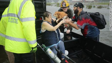 In James City, North Carolina, rescuers help a woman and her dog from their flooded home on Friday.