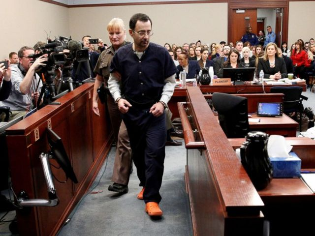 PHOTO: Larry Nassar, a former team USA Gymnastics doctor who pleaded guilty in Nov. 2017 to sexual assault charges, is escorted into the courtroom during his sentencing hearing in Lansing, Mich., Jan. 24, 2018.