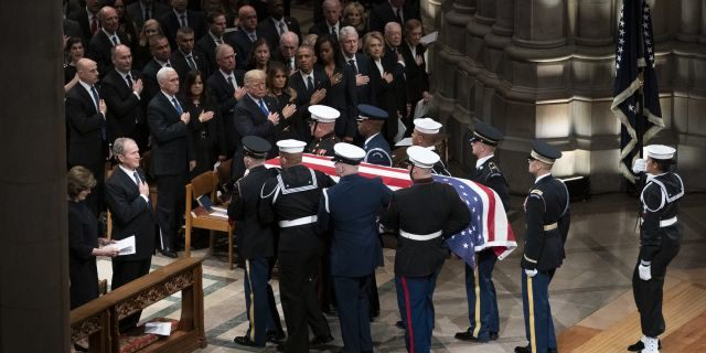 The flag-draped casket of former President George H.W. Bush is carried by a military honor guard past former President George W. Bush and his wife Laura Bush , President Donald Trump, first lady Melania Trump, former President Barack Obama, Michelle Obama, former President Bill Clinton, former Secretary of State Hillary Clinton, former President Jimmy Carter, and Rosalynn Carter at the conclusion of a State Funeral at the National Cathedral, Wednesday, Dec. 5, 2018, in Washington. (AP Photo/Carolyn Kaster)