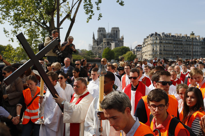 Religious officials carry the cross during a Good Friday procession in Paris on April 19, 2019.