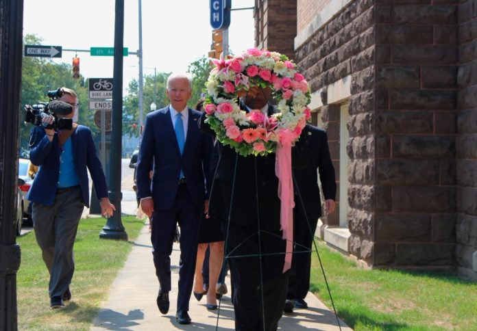 Former Vice President and presidential candidate Joe Biden, center left, joins Sen. Doug Jones and Birmingham Mayor Randall Woodfin at a wreath laying after a service at 16th Street Baptist Church in Birmingham, Ala., Sunday, Sept. 15, 2019. Visiting the black church bombed by the Ku Klux Klan in the civil rights era, Democratic presidential candidate Biden said Sunday the country hasn't