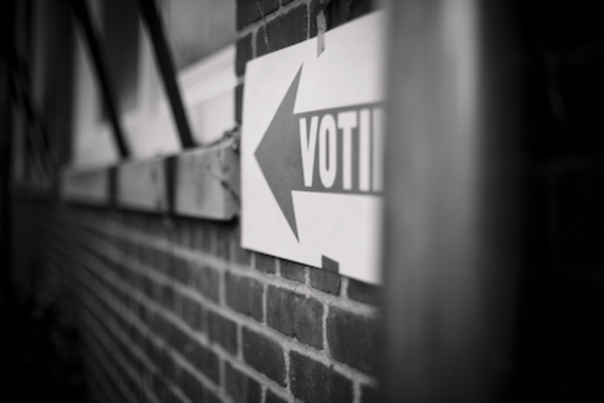 """A sign reads """"voting"""" directs residents to a polling location"""