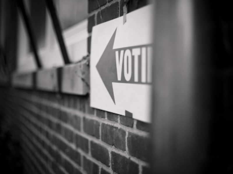 "A sign reads ""voting"" directs residents to a polling location"