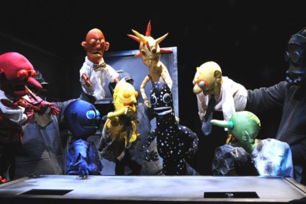 """The Gravity Bar scene from """"Baby Universe (A Puppet Odyssey),"""" presented by Wakka Wakka. This photo is of the puppet Baby Universe (center, black with white spots, which are stars), from left to right: Mars (red); Earth (blue); Mercury (orange, above the Earth); Venus (yellow with cigarette); Meteorite (with spikes); Jupiter (yellow with blue eyes); and Neptune (green). (The puppeteers wear gas masks.) """"Baby Universe"""" is written and directed by Kirjan Waage and Gwendolyn Warnock, featuring over 30 expressive hand-and-rod puppets created by Mr. Waage. The production is being presented at Baruch Performing Arts Center, 55 Lexington (enter on 25th Street just east of Lexington). Performances run from December 1, 2010 through January 8, 2011. The five puppeteers are: Melissa Creighton, Andrew Manjuck, Peter Russo, Kirjan Waage, and Gwendolyn Warnock. Photo by: Jim Baldassare. Press contact: Jim Baldassare, jbpressrep@aol.com, 212-362-3346."""