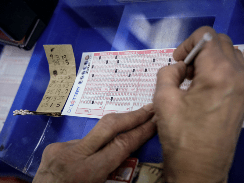A woman fills out her D.C. Lottery Powerball slip.