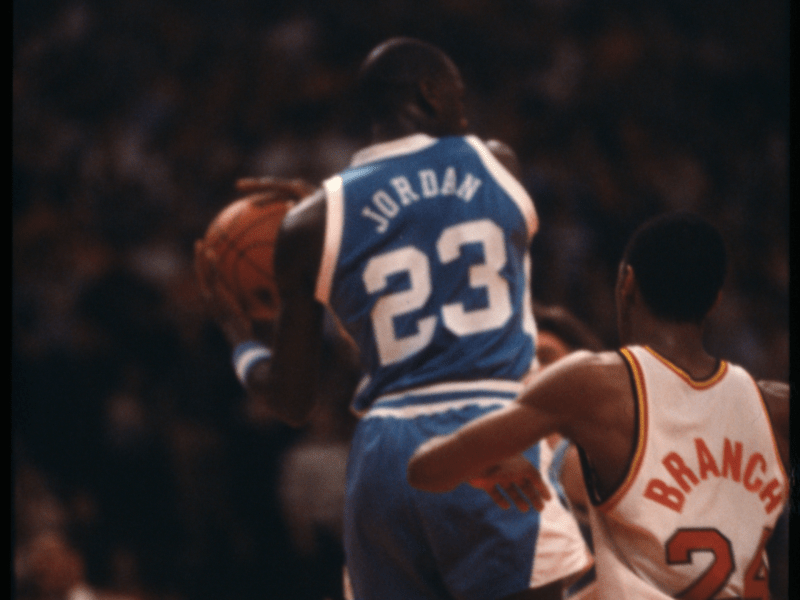 Michael Jordan rebounding the ball against Marylands Adrian Branch during their colleges yearss Adrian Branch during their colleges years