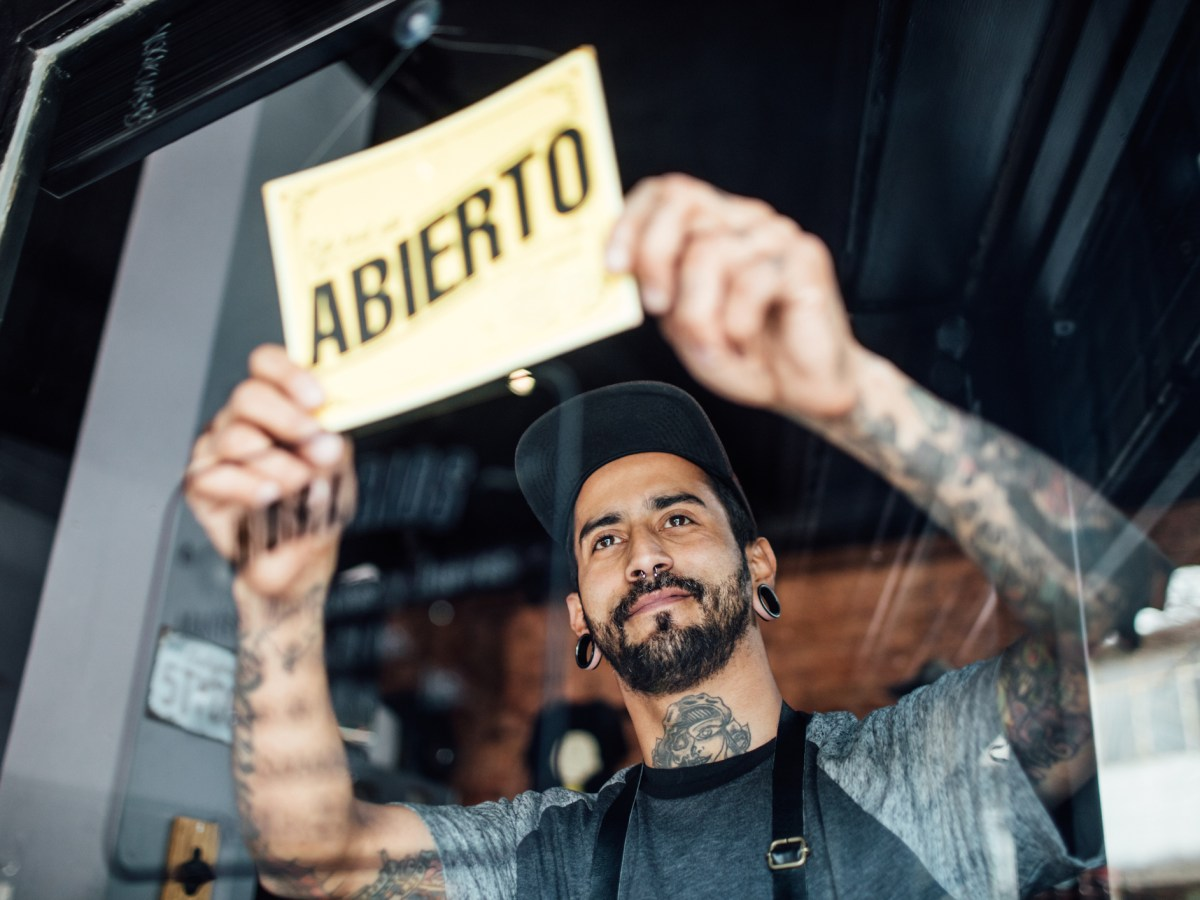 Low angle view of mid adult barber hanging an open sign on door. Male owner is holding abierto sign seen through glass. He is working in hair salon.