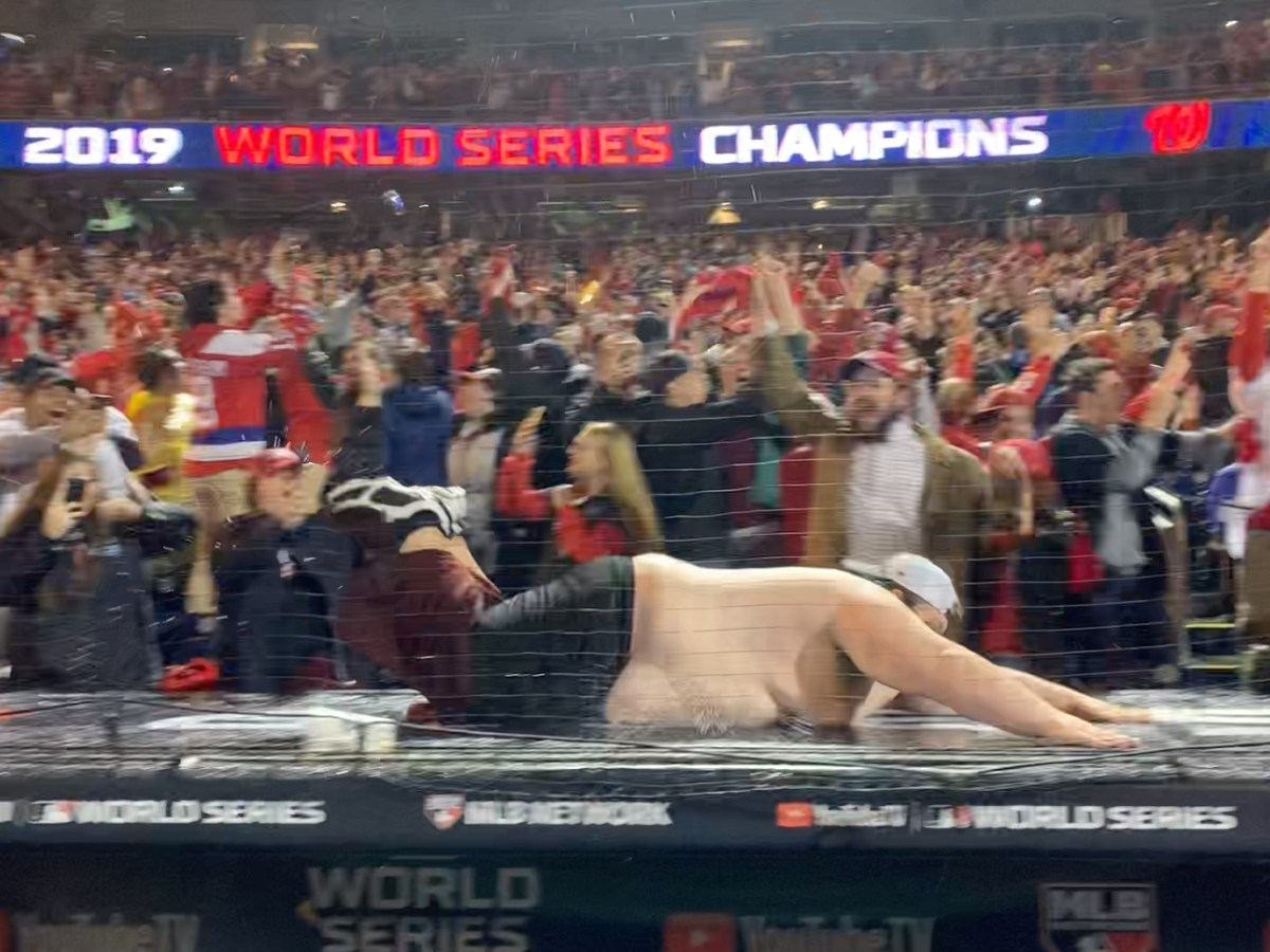 Jason Turner slides across the Nationals dugout after they won the World Series