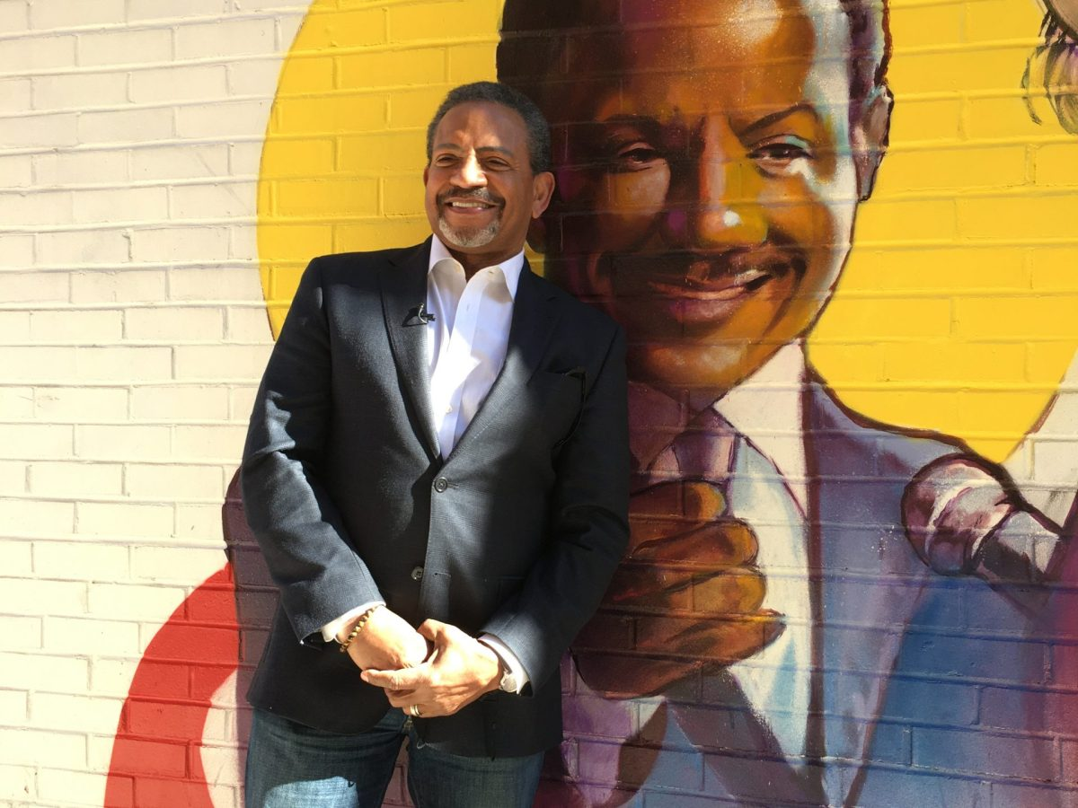 Bruce Johnson stands in front of the mural depicting him.