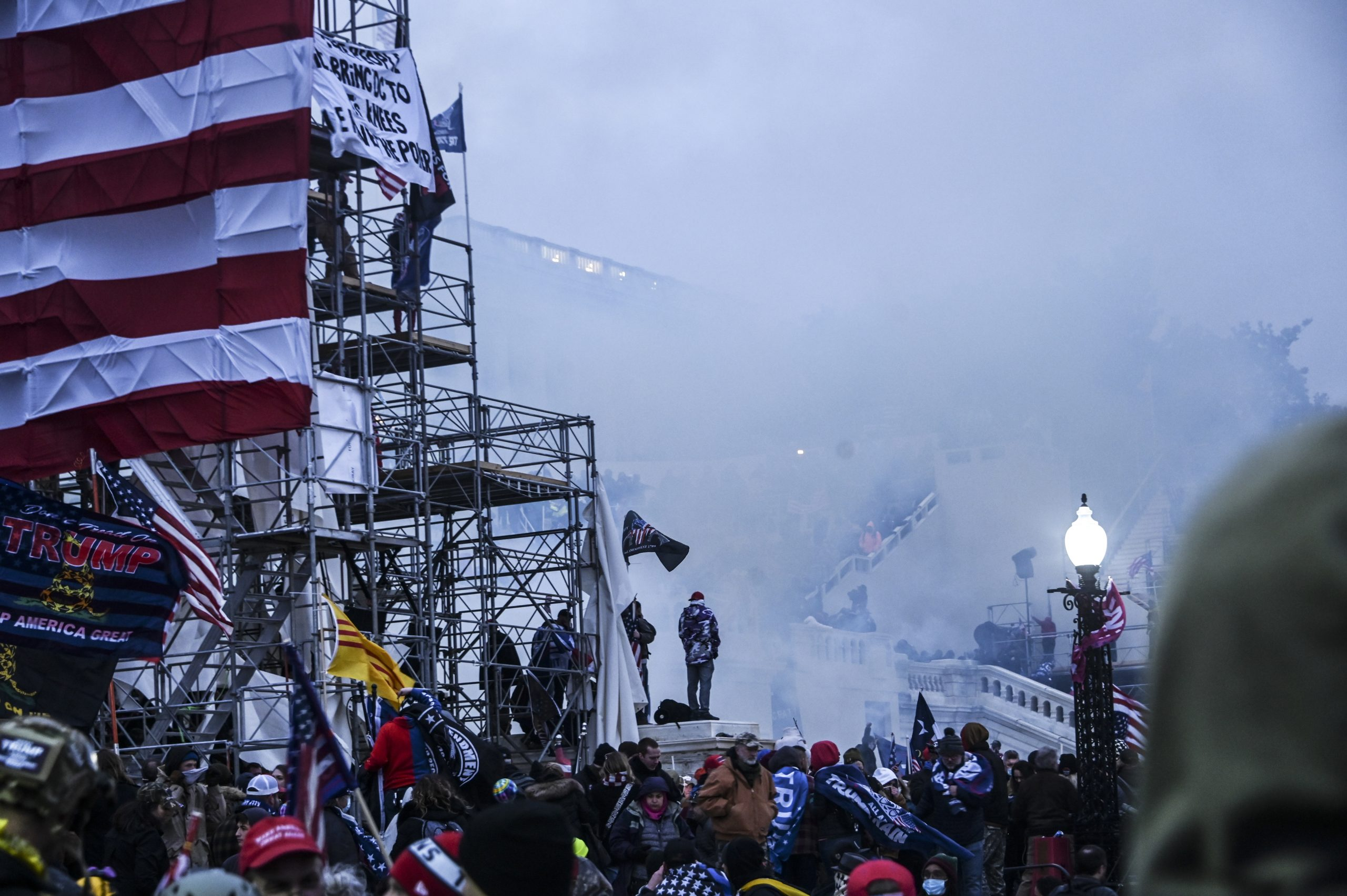 Tear gas is deployed to clear the protestors from the inauguration scaffolding on the Capitol's north side.