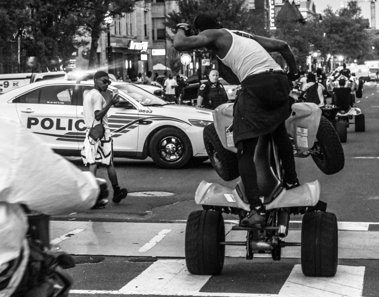 A young man pops a wheelie to pose for a photo at the first Moechella on 14th & U Streets NW.