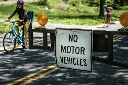 """Sign in foreground reading """"No motor vehicles"""" and cyclists in background"""