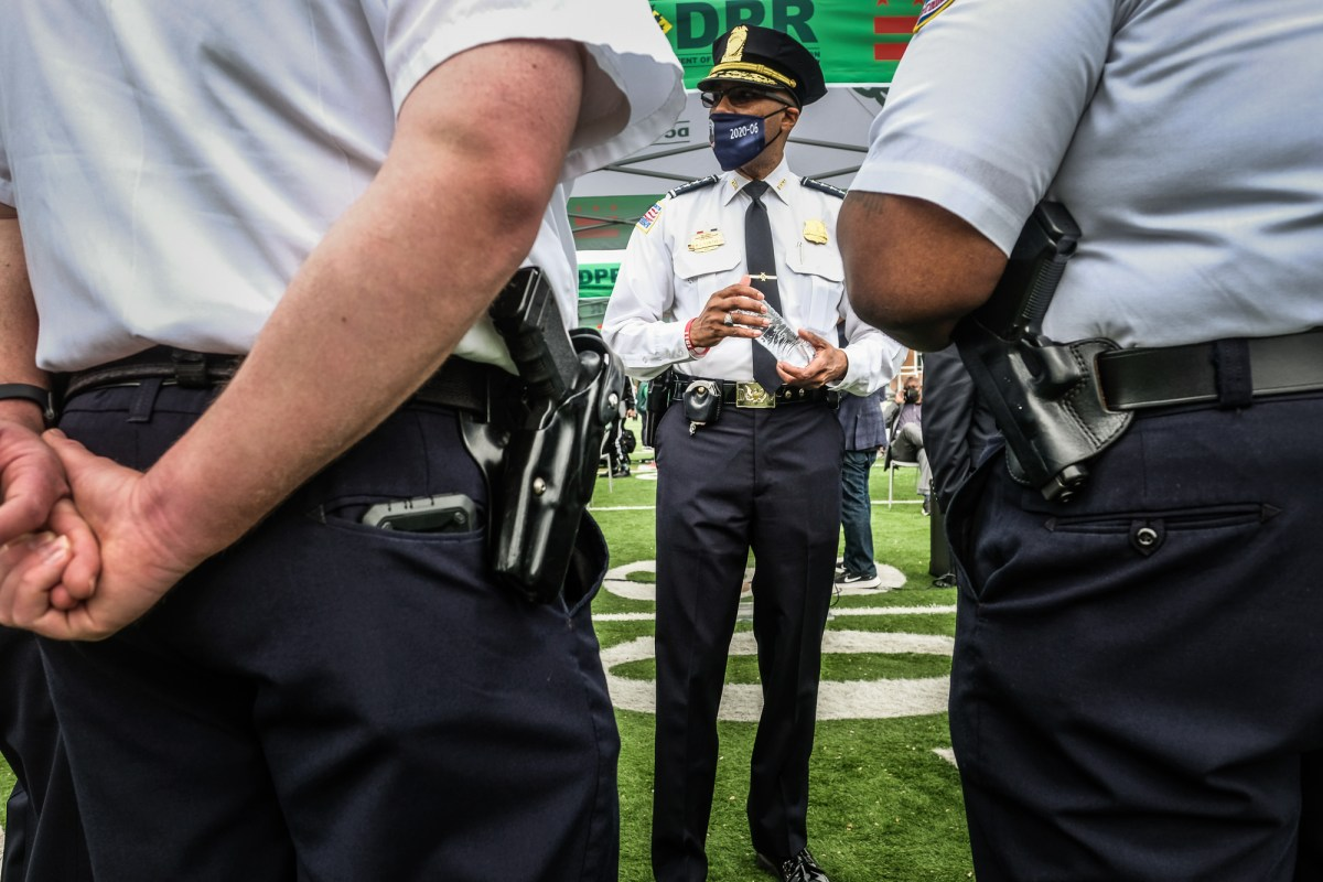 Police chief Robert Contee standing masked flanked by two officers in foreground