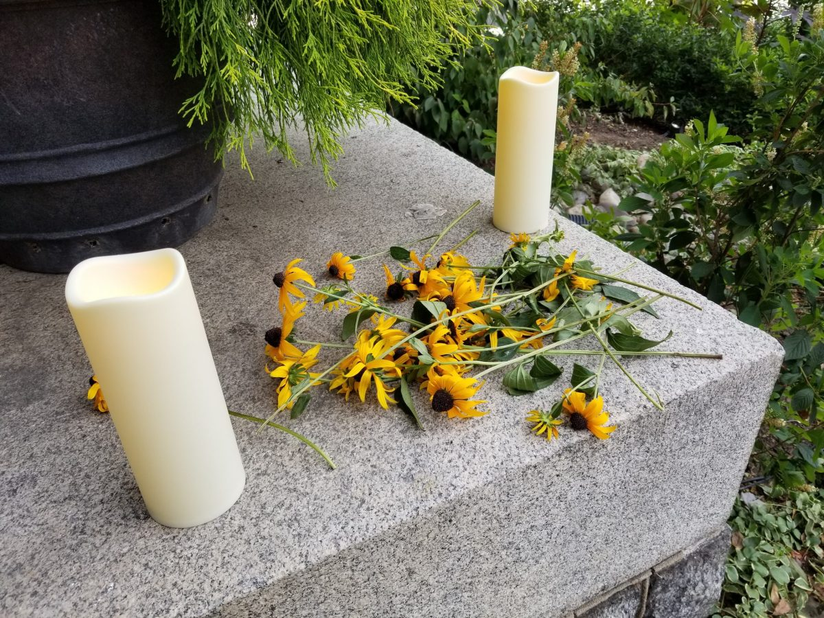 Sunflowers offered by vigil attendees honor the 43 people who died while homeless in D.C.