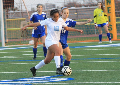 Sophomore Colbi Edmonds dribbles the ball as she keeps the defender from Mac at bay. Photo by Meredith Kershaw.